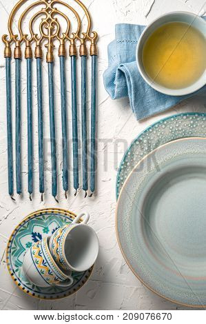Hanukkah with candles, plates, butter in a bowl and blue napkin top view vertical