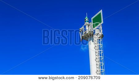 beacon of the sea equipped with camera and GSM antennas on blue sky