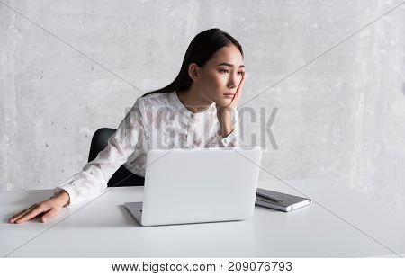 Yearning young lady is locating at workplace and looking aside with wistful sight. Portrait. Copy space on left side