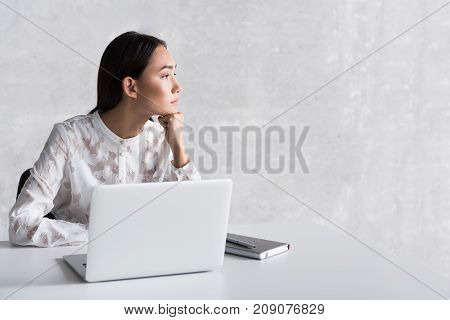 Wistful woman sitting near desk and looking aside with depression in her eyes. Open laptop in on countertop. Profile. Copy space on right side