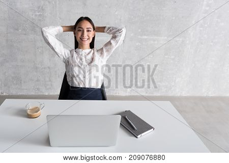 Ready for job. Hilarious businesswoman is siting near desk and looking at camera with wide smile. Portrait. Copy space on right side
