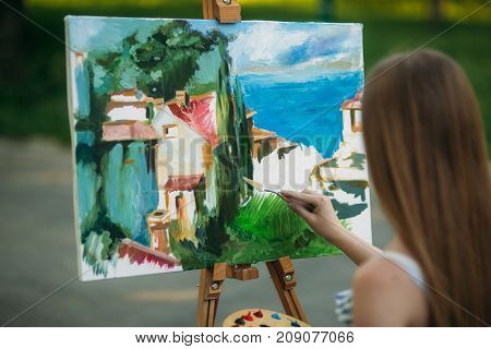Beautiful girl draws a picture in the park using a palette with paints and a spatula. Easel and canvas with a picture