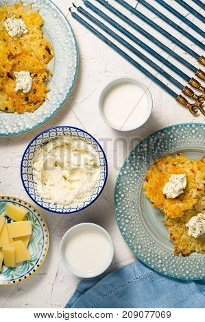 Latkes, milk and cheese cheese, Hanukkah on a white table vertical