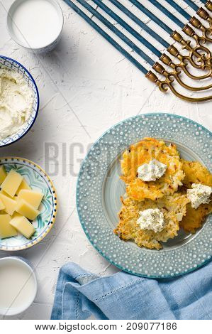 Latkes, cheese, milk and curd cheese, Hanukkah on white table free space vertical