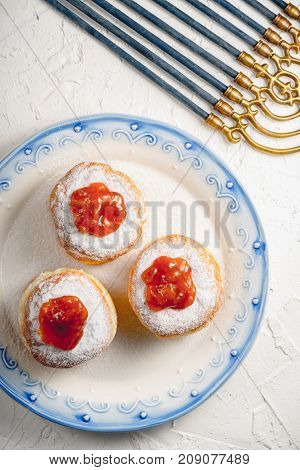 Donuts with jam on a plate with a blue rim and Hanukkah closeup vertical