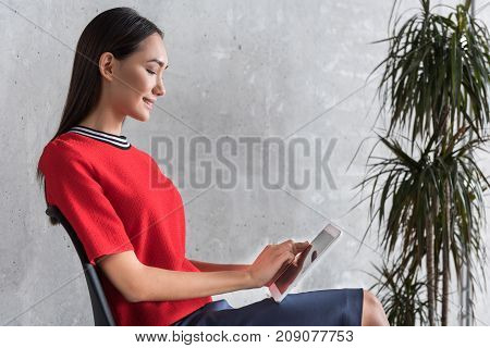 Joyful woman is working at tablet. She sitting on chair near plant. Profile