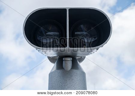 Tourist binocular telescope over cloudy sky background