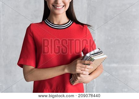 Hilarious woman is standing near grey wall and holding notebooks. Focus on female smile