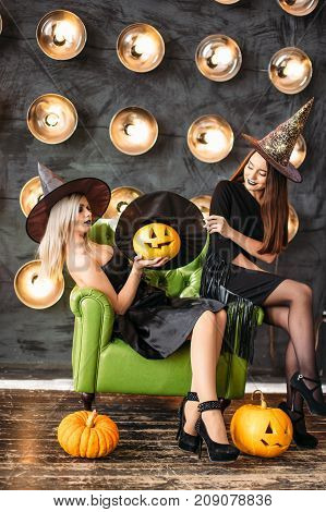 Two Women In Halloween Costumes On Party Sitting On Chair Over Bulb Background