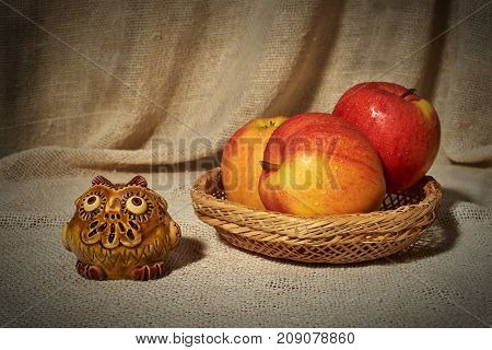 Still life with ceramic handmade owl and apples in a small wicker basket on the background of a curtain of coarse cloth. On fruits are drops of water