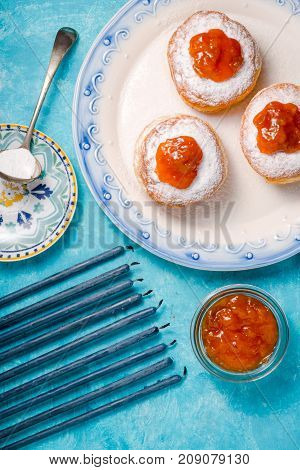 Blue candles, a plate with donuts and jam on a turquoise table close-up vertical