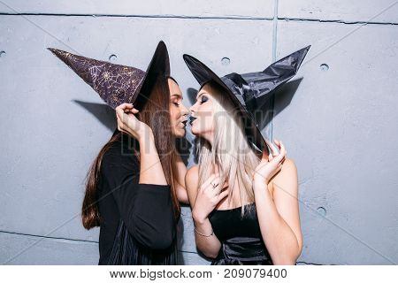 Two Happy Young Women In Black Witch Halloween Costumes On Party