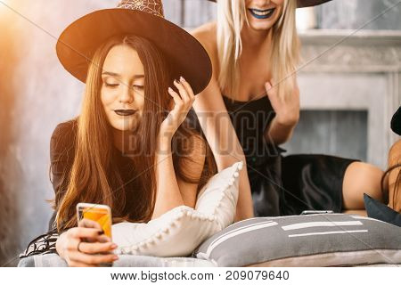 Beautiful Girls In Black Dresses And Witch Hats Using Smart Phone