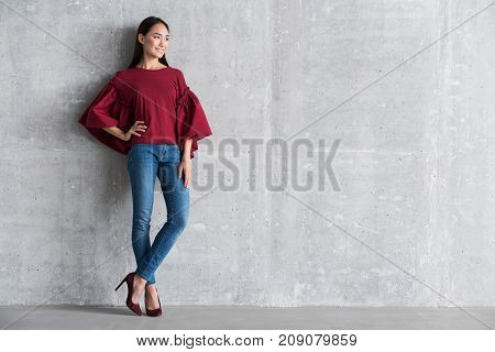 Feeling confident. Full length portrait of cheerful stylish young asian woman is leaning on wall and looking aside with smile. Copy space in the right side