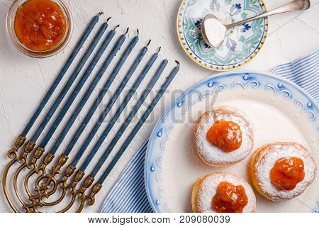 Donuts with apricot jam on a ceramic plate and Hanukkah top view horizontal