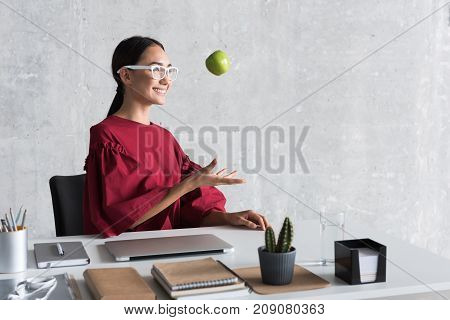 Playful mood. Joyful young asian girl in glasses is tossing apple with smile. She is sitting at her workplace and expressing satisfaction. Copy space in the right side