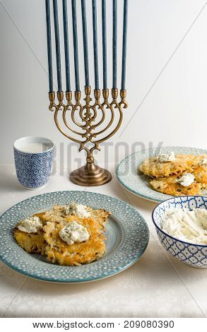 Latkes on a plate, Hanukkah, cups with milk on a white tablecloth side view vertical