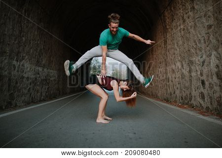 Man leapfrog jumping over woman on a road