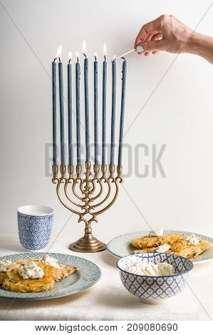 Hanukkah with lighted candles, latkes on a plate, curd cheese vertical
