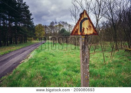 Rusty turn sign next to country road in Kampinos Forest near Warsaw Poland