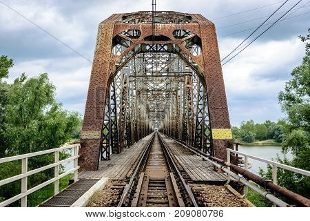 Rusty steel railroad bridge over Vistula River in Gora Kalawaria Masovian Province of Poland