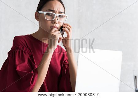 Unpleasant call. Low angle of hopeless girl is talking on phone while expressing frustration. She is sitting at table with laptop and touching her lips while looking down disappointedly. Copy space