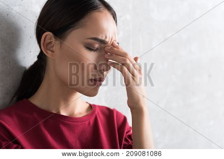 Awful headache. Close-up of face of attractive business lady who is in great pain. She is touching her head and expressing suffering while leaning on wall with closed eyes. Copy space