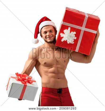 Best wishes to you. Cropped portrait of a young male with muscular sexy body wearing Santa Claus hat giving a gift box to a viewer