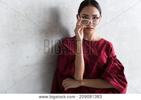 Business lady. Portrait of elegant young woman in glasses is leaning on wall and looking at camera thoughtfully. Copy space in the left side
