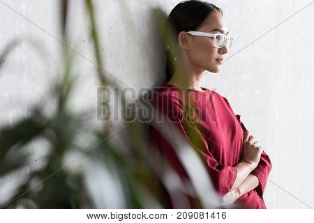 Pensive look. Profile of stylish asian woman in glasses is leaning on wall with crossed arms and looking aside thoughtfully. Copy space in the left side. Selective focus