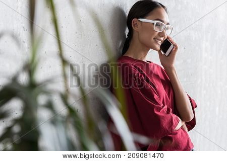 Pleasant conversation. Cheerful fascinating young asian woman is talking on modern smartphone while leaning on wall and expressing gladness. Copy space in the left side. Selective focus