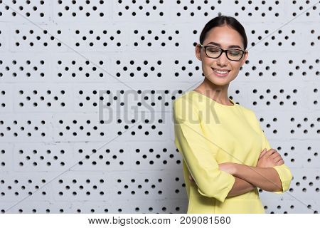 Professional businesswoman. Waist-up of confident elegant young woman in glasses is standing with crossed arms and looking down with smile. Copy space in the left side
