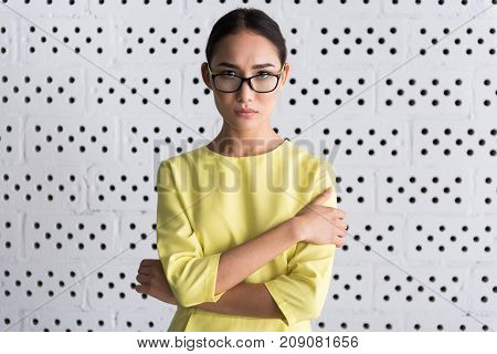 Can not find solution. Waist up portrait of young woman in glasses is standing with crossed arms and looking at camera with disappointment