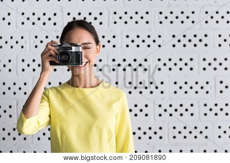 Photographer pose. Young attractive professional woman is standing in pose of making pictures while holding her camera and expressing gladness. Copy space in the right side
