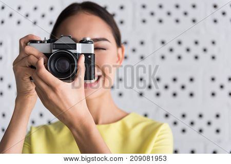 Say cheese. Close-up of photo camera in hands of joyful woman. She is making picture with smile. Focus on device. Copy space in the right side