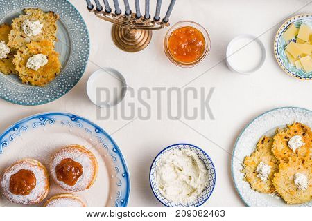 Plates with latkes, donuts, curd cheese for a festive feast horizontal