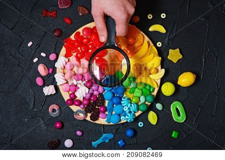 Colorful rainbow color candy bar with hand holding magnifier. . Top view.