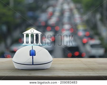 Bank icon with wireless computer mouse on wooden table over blur of rush hour with cars and road Business banking online concept