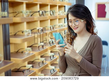 Beautiful young asian woman holding smartphone for buying online glasses spectacles fashion in optical shop market