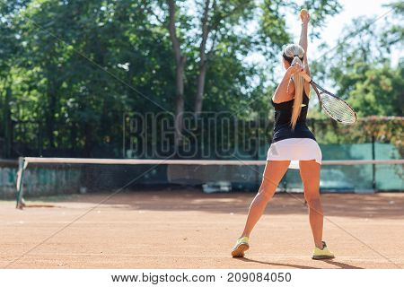Full body image of blonde young woman tennis player in action in a tennis court indoor. Photo of the girl is made from the back. Woman tennis player dressed white skirt, black T-shirt and black cap