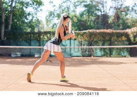 Full body photo of sexy young lady tennis player in action in a tennis court indoor. Photo of the woman is made from the back. Blonde tennis player dressed white skirt, black T-shirt and black cap