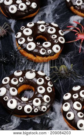 Donuts with chocolate icing decorated googly eyes on Halloween