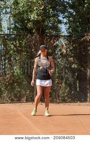 Full body image of caucasian blonde female tennis player with ball on court outdoor at the park. White woman dressed white shorts, black T-shirt and black cap and ready to start game