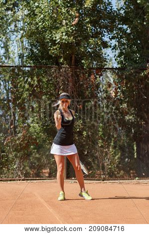 Full body Vertical photo of female tennis player in action on a court outdoor. Tennis ball in hand. Ready to start game