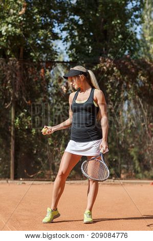 Full body vertical photo of amazing smiling woman tennis player in action on a court outdoor. Tennis ball in right hand. Ready to start game and win