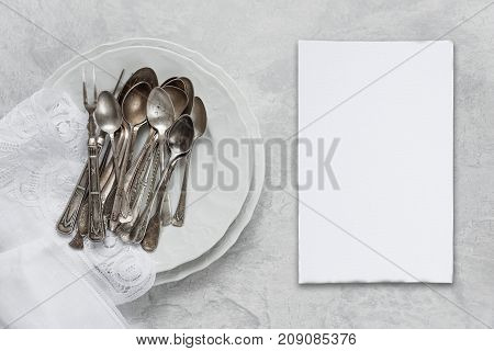 Various silverware on a porcelain plate white napkin with Belgian lace and white blanc paper card are on the background of gray concrete surface with copy-space