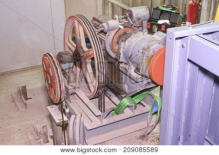 Part of industrial lift. Pulley wheel and engine  in engine room. Reconstruction of industrial lift.