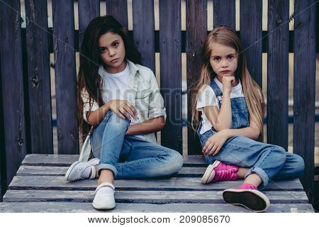 Little pretty girls outdoor. Fashionable children posing on the background of wooden fence.