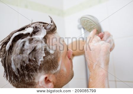 Turn off the water or break the shower. A young man with a soapy head is standing in the bathroom and looks at the shower with perplexity.