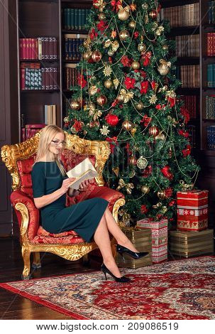 christmas x-mas winter happiness concept . Happy young lady blonde is reading a book near the Christmas tree.